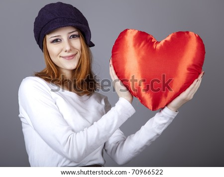 Beautiful red-haired girl in cap with toy heart. - stock photo