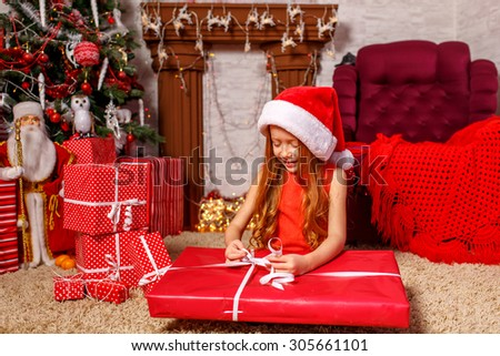 Beautiful red-haired girl in santa hat opening gift near Christmas tree  - stock photo