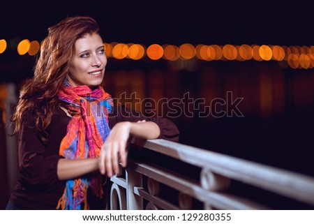 beautiful red-haired girl in the night city - stock photo