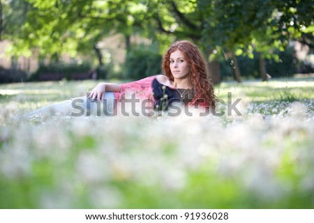 Beautiful red haired girl laying on the green grass and flowers - stock photo