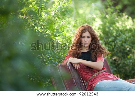 Beautiful red haired girl sitting in the park on a bench. - stock photo