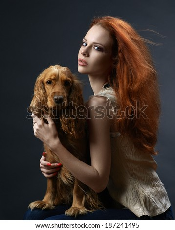 beautiful red-haired girl with a dog in the dark blue background