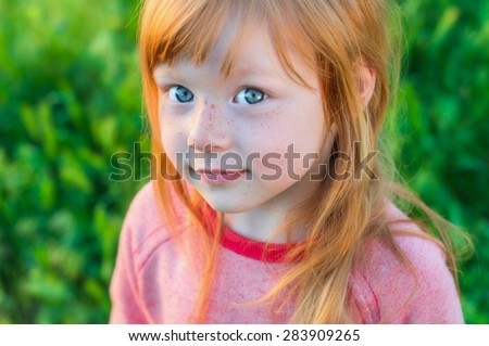 beautiful red-haired girl with big piercing gray eyes against the background of green field - stock photo