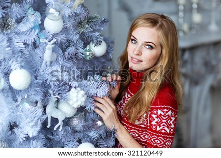 Beautiful red-haired girl with freckles in red sweater with white ornaments stands near a tree in the New year and smiles - stock photo