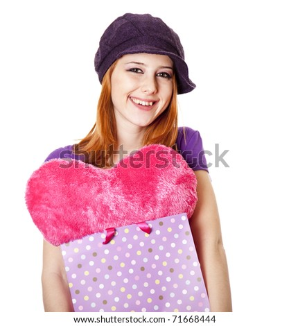 Beautiful red-haired girl with heart in bag. Studio shot.