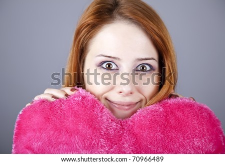 Beautiful red-haired girl with toy heart. - stock photo