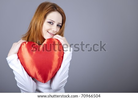 Beautiful red-haired girl with toy heart.