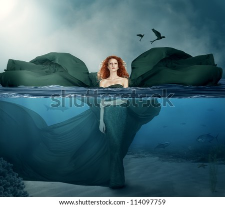 beautiful red haired goddess standing in the water.manipulated. - stock photo