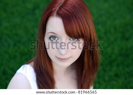 beautiful red haired teen girl with freckles in grass - stock photo