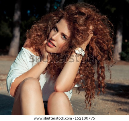 beautiful red haired with long curly , shine hair and make up posing on a sunny day. Horizontal , outside shot. - stock photo