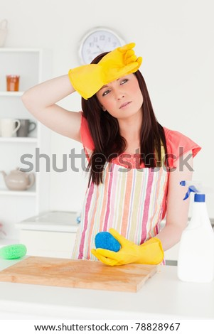 Beautiful red-haired woman cleaning a cutting board in the kitchen in her apartment