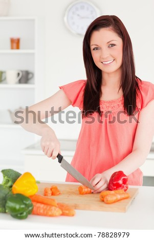 Beautiful red-haired woman cutting some carrots in the kitchen in her apartment