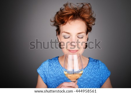Beautiful red haired woman drinking and enjoying white wine. Female model having alcohol. Space for copy. - stock photo