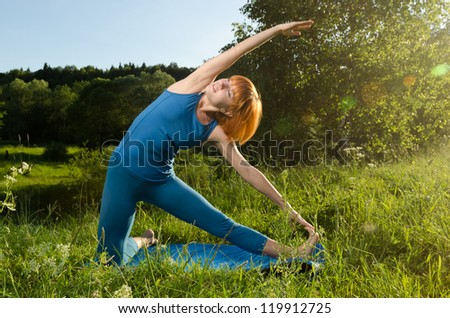 Beautiful red haired woman practicing fitness yoga outdoors on a summer day - stock photo