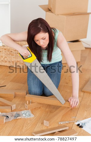 Beautiful red-haired woman using a saw for diy at home - stock photo