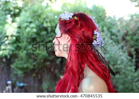 beautiful red haired woman with flowers in her hair, natural background.