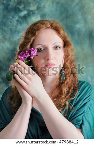beautiful red-haired woman with orchid - stock photo