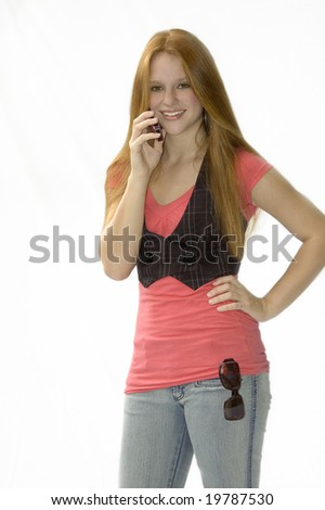 Beautiful red head standing with her hand on her hip talking on a cell phone