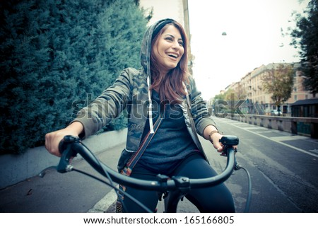 beautiful red head woman on bike in the city - stock photo