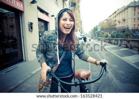 beautiful red head womanon bike in the city - stock photo