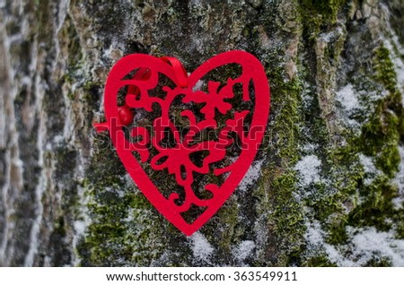 Beautiful red heart on a snowy tree trunk. Concept of love and St. Valentines Day. - stock photo