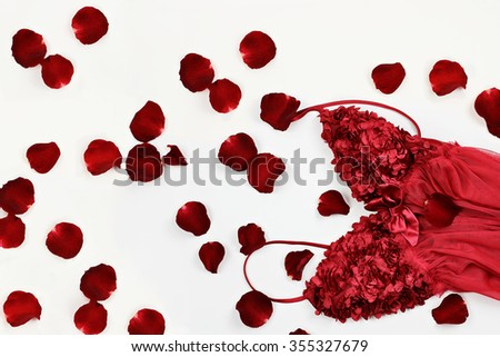 Beautiful red lingerie surrounded by rose petals for Valentines Day. - stock photo