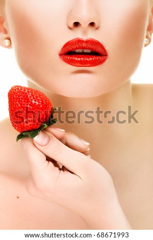 Beautiful red lips with strawberry - stock photo