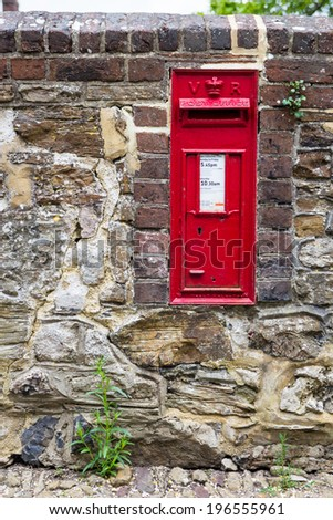Beautiful red mailbox built into a stone wall seen in Rye, Kent, UK. - stock photo