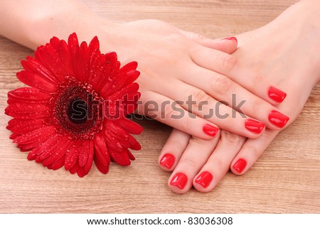 beautiful red manicure and  flower on a wooden background