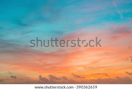 Beautiful red orange sky during sunset. Small clouds orange and gold clouds in the middle and blue sky on top. Background texture.  - stock photo