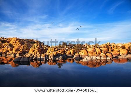 Beautiful red rock mountains reflecting in the water along the shore of Watson Lake in Prescott, Arizona, USA. - stock photo