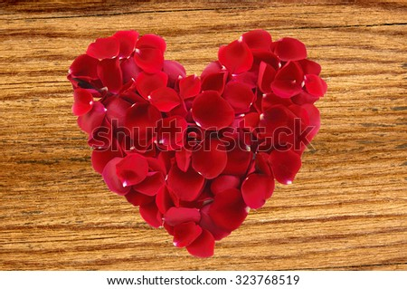 beautiful red rose petals as heartsymbol on wooden background - stock photo
