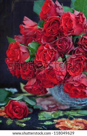 Beautiful red roses in a vase on a table. - stock photo