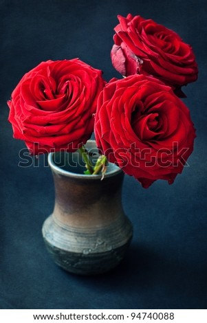 beautiful red roses in an old pot on a dark background - stock photo
