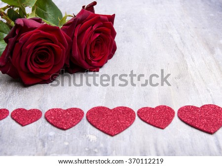 beautiful red roses on wooden background with heart