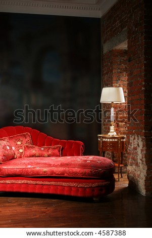 Beautiful red sofa and lamp at a wall from a brick - stock photo