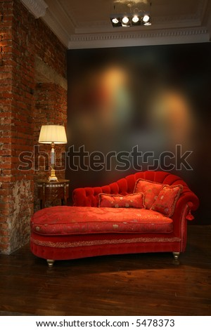 Beautiful red sofa and lamp at a wall from a brick