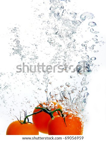 Beautiful red tomato falls into water - stock photo