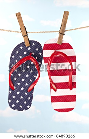 Beautiful red, white and blue flip flop thong shoes hanging on jute clothesline attached with wooden clothespins - stock photo