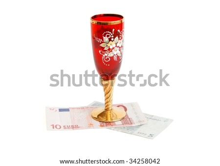 Beautiful red wine glass  with golden stem on euro bills isolated - stock photo