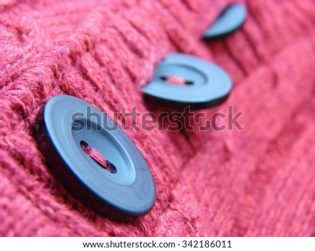 beautiful red winter sweater with and buttons, texture background; shallow depth of field