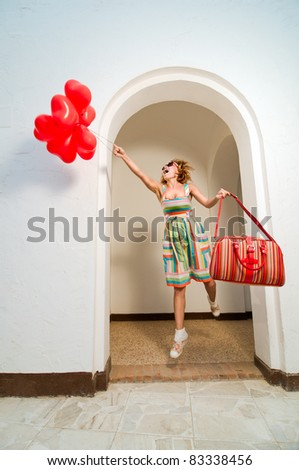 Beautiful red woman with lots of heart shaped baloons - stock photo