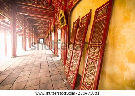 Beautiful red wooden hall with golden ornate details in Hue citadel, Vietnam, Asia. Vanishing roof and tiled floor. Sunlight through columns. Famous destination for tourists. UNESCO Heritage site.