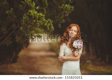 Beautiful redhair bride outdoors in a forest.  - stock photo
