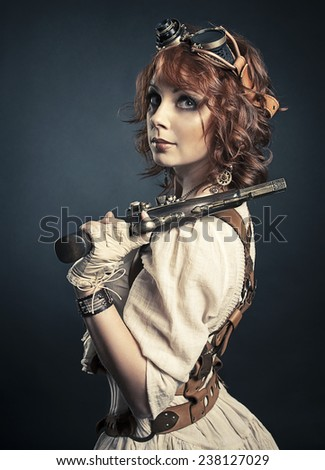 Beautiful redhair steampunk girl with gun looking at camera - stock photo