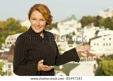 beautiful redhaired business woman broker shows real estate - stock photo