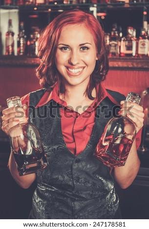 Beautiful redhead barmaid behind bar counter - stock photo