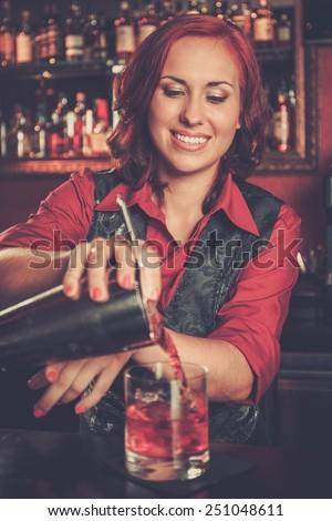 Beautiful redhead barmaid making cocktail - stock photo