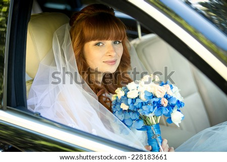 Beautiful redhead bride sitting in car and holding blue wedding bouquet - stock photo