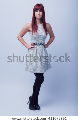 Beautiful redhead female in summer dress over white background - stock photo